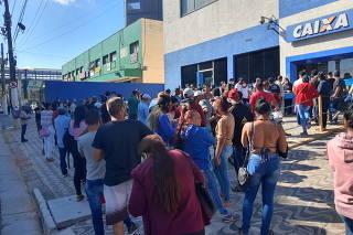 Pessoas esperam em fila para sacar auxílio emergencial na agência da Caixa