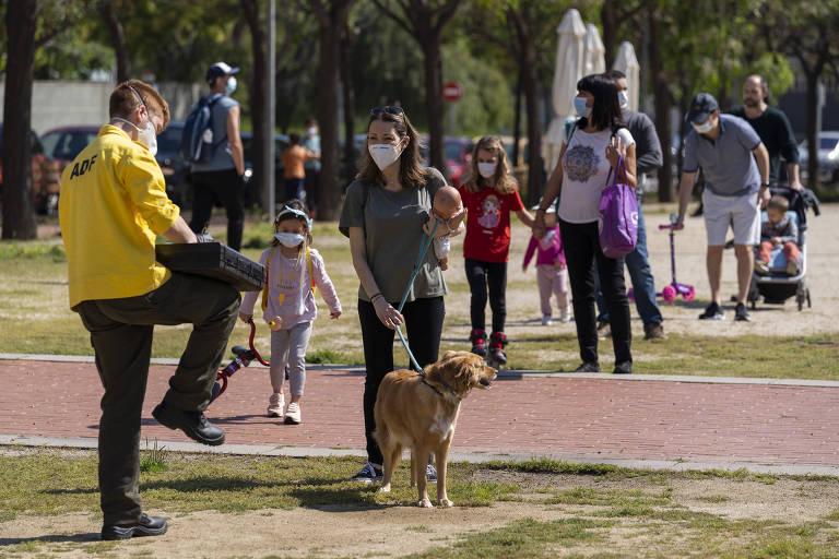 Voluntário registra crianças e seus pais com autorização para saírem de casa em Molins de Rei, próximo a Barcelona