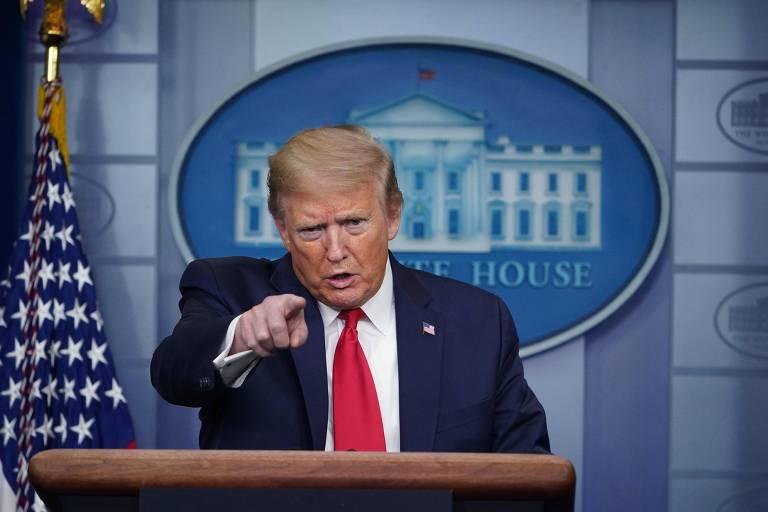 Donald Trump com bandeira e símbolo da Casa Branca ao fundo aponta para um repórter