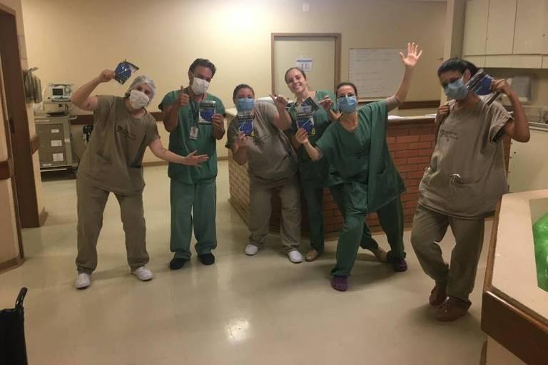 Seis funcionários estão em um corredor do hospital; eles estão uniformizados e mascarados, sorrindo e fazendo pose para foto