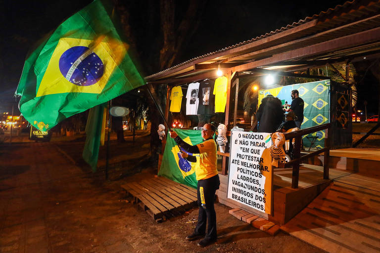 Manifestante pró-Lava Jato agita bandeira do Brasil em acampamento montado em frente ao prédio da Justiça Federal em Curitiba, em 2017, onde trabalhava o então juiz Sergio Moro
