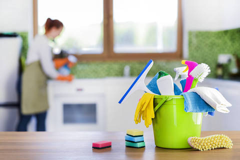 Cleaning items on wooden table in modern kitchen. Woman house work or charwoman blured in background. Bucket, brush, washcloth, spray..
