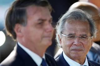 Brazil's Economy Minister Paulo Guedes listens to Brazil's President Jair Bolsonaro, while leaving Alvorada Palace in Brasilia