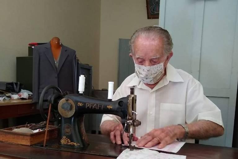 O alfaiate Cláudio Menegatti em sua máquina de costura
