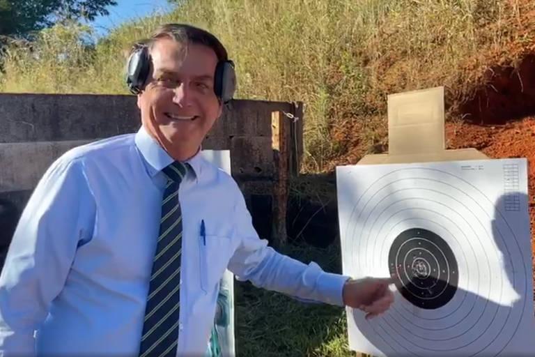 O presidente Bolsonaro mostra alvo atingido por ele em clube de tiro em Brasília