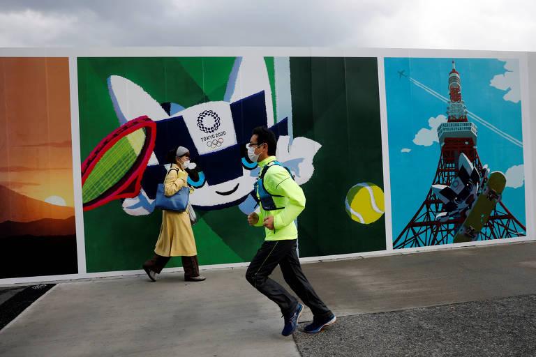 Homem corre em frente a pôster com a mascote dos Jogos de Tóquio