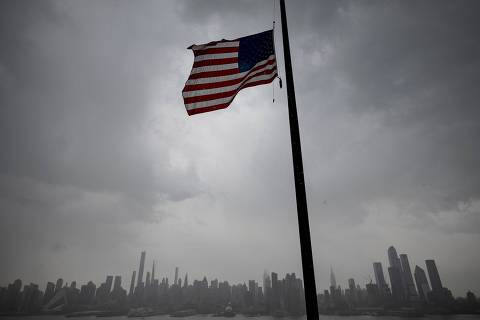 TOPSHOT - An US flag  flies at half-mast half mast in front of the Skyline of Manhattan of New York City seen from Weehawken, New Jersey, on April 21, 2020. - Over 2.5 million people have been confirmed to have contracted the coronavirus worldwide, with 80 percent of cases in Europe and the United States, according to an AFP tally Tuesday based on official figures. (Photo by Johannes EISELE / AFP) ORG XMIT: EIS