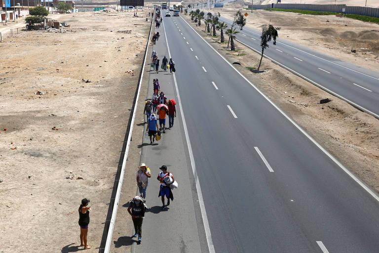 Peruanos caminham pela estrada Panamericana para tentar tomar ônibus para deixar Lima em meio à pandemia de coronavírus