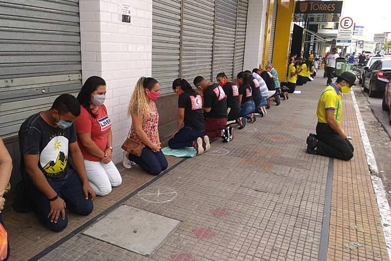 No centro de Campina Grande, funcionários protestam ajoelhados pela reabertura do comércio