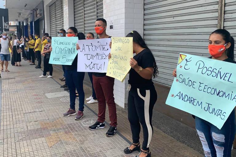 Manifestantes exibiram cartazes com frases, cantaram o hino nacional e rezaram de joelhos em frente às lojas fechadas