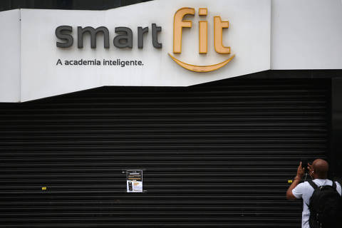 A man takes pictures of a notice inviting people to join Smart Fit gym's online workout classes at home, released free to view on their website, YouTube and social media sites as the gym suspends training sessions as a protective measure to prevent the spread of the novel coronavirus disease (COVID-19) in Sao Paulo, Brazil March 19, 2020. REUTERS / Rahel Patrasso ORG XMIT: GGG-RP02