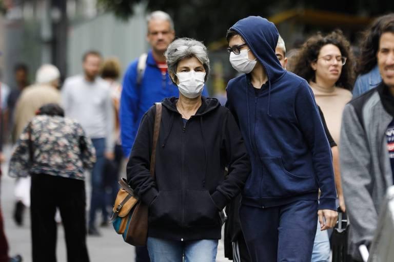 Pessoas caminham em São Paulo usando máscaras para se protegerem do coronavírus