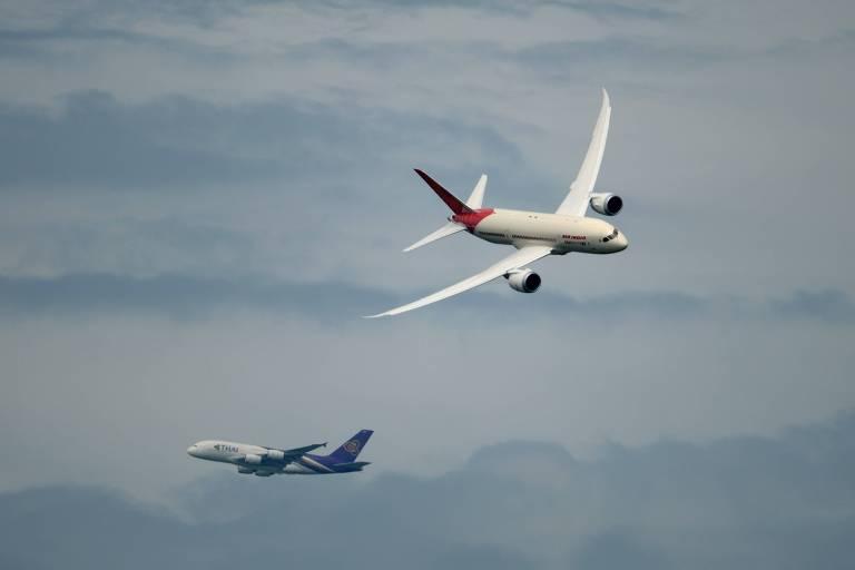 Um Boeing 787 voa com um Airbus A380 ao fundo durante feira aeroespacial na França