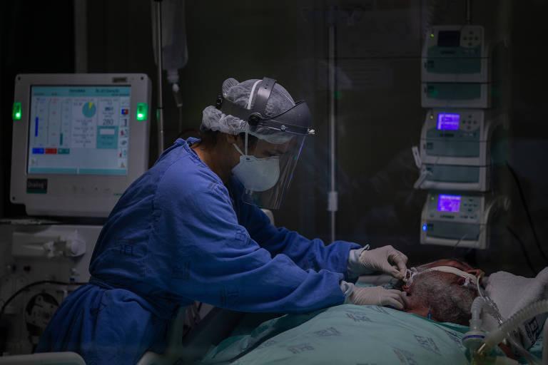 Enfermeira do Instituto de Infectologia Emílio Ribas observa paciente com Covid-19 na UTI