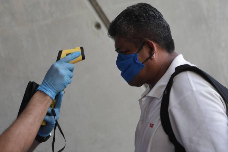 Médico checa a temperatura de espectador na entrada de evento de boxe em Manágua