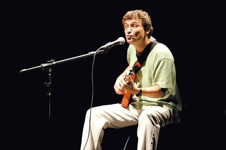 Músico vestido com camiseta verde e calça cáqui tocando violão e cantando ao microfone
