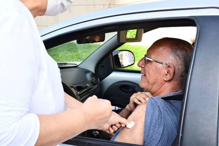 Senhor recebe vacina contra gripe, dentro de seu carro