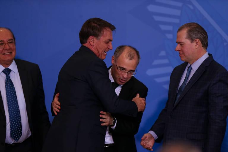 Ao lado de Gilmar Mendes (esq.) e Dias Toffoli, do STF, presidente Jair Bolsonaro abraça o novo ministro da Justiça, André Mendonça, em sua cerimônia de posse, nesta quarta-feira (29)