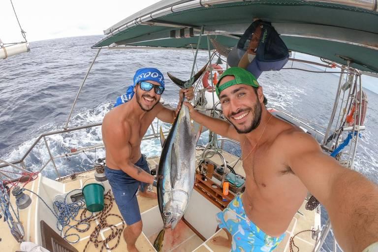 Dois homens sem camisa em barco, um segura um peixe