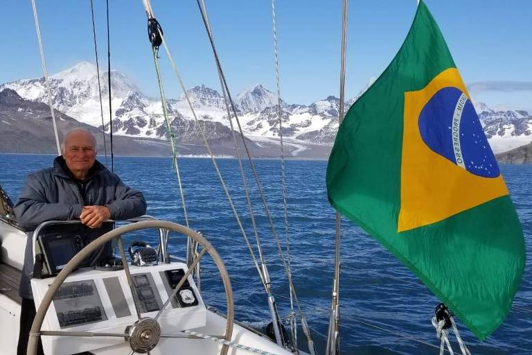 Homem idoso em leme de barco com a bandeira do Brasil