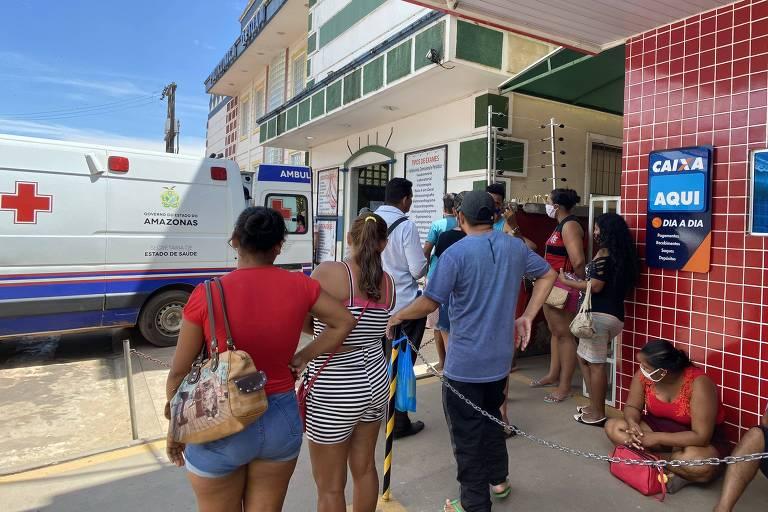 Diante do posto da Caixa, beneficiários do auxílio emergencial observam a chegada de paciente ao hospital de campanha de Manacapuru (AM)