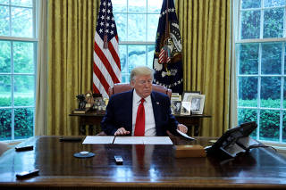 U.S. President Trump looks at briefing papers during interview with Reuters in the Oval Office of the White House in Washington
