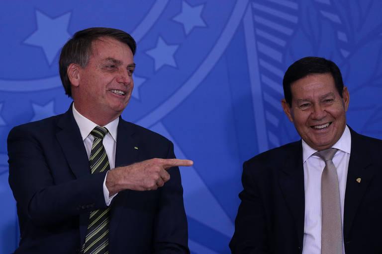 O presidente Bolsonaro aponta para o vice, general Hamilton Mourão, durante evento no Palácio do Planalto