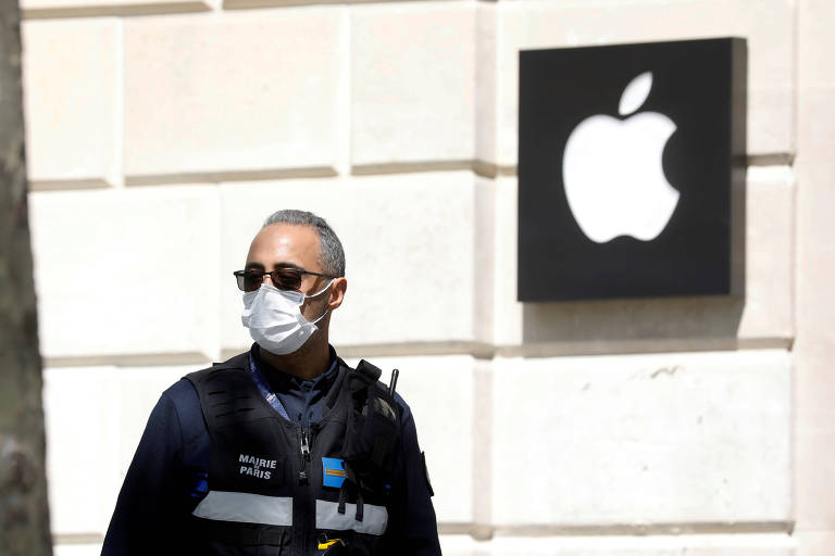Pessoa com máscara em frente à loja da Apple na Europa; coronavírus afetou demanda e produção de iPhones