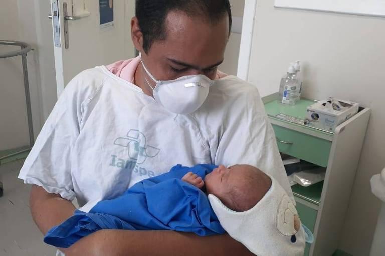 Fernando Alves da Silva, 35, com seu filho Murilo no colo