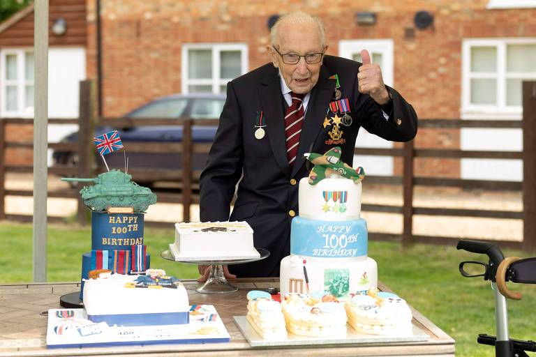 Capitão Tom Moore posa diante de uma mesa com bolos de aniversário decorados em comemoração pelos seus 100 anos