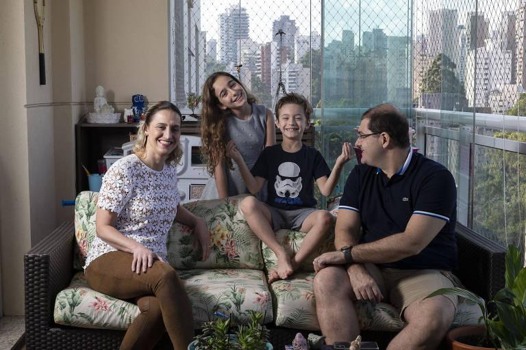 Família com dois adultos e duas crianças em varanda
