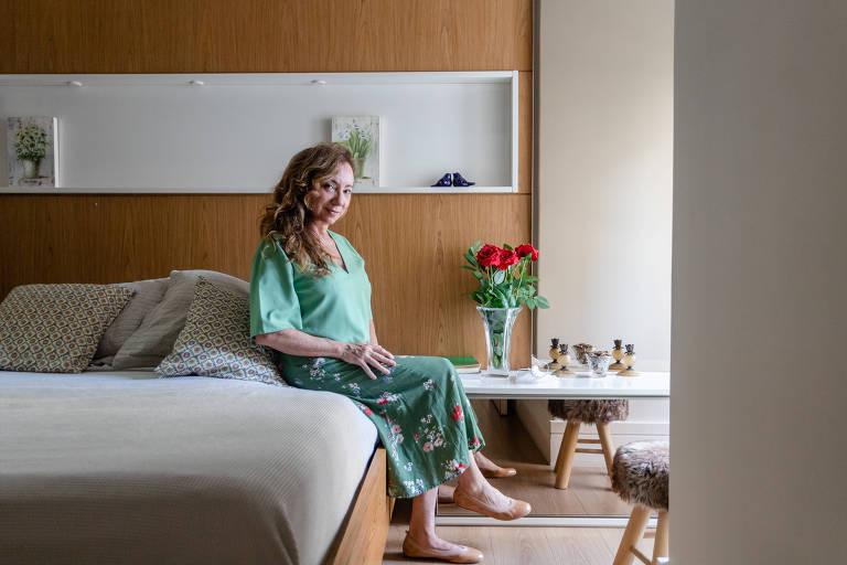 Mulher sentada em cama, em quarto