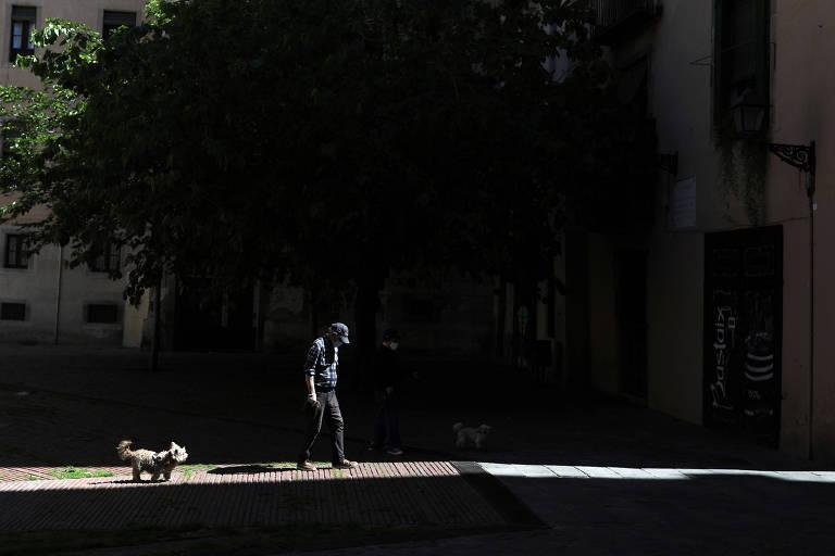 Homem com máscara caminha com cachorro em Barcelona