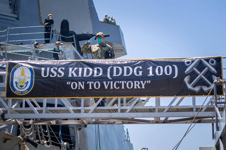 Marinheiro americano com máscara faz saudação do USS Kidd, retirado de combate