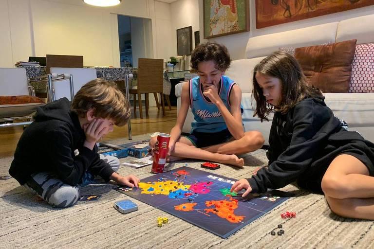Felipe, 7, João Pedro, 13, e Catarina, 7, jogam War em casa