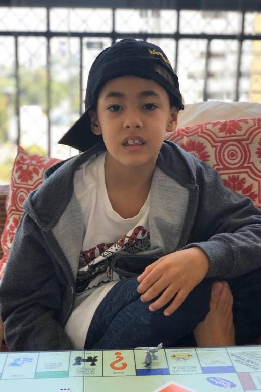 Pedro, 7, joga Banco Imobiliário na varanda de casa