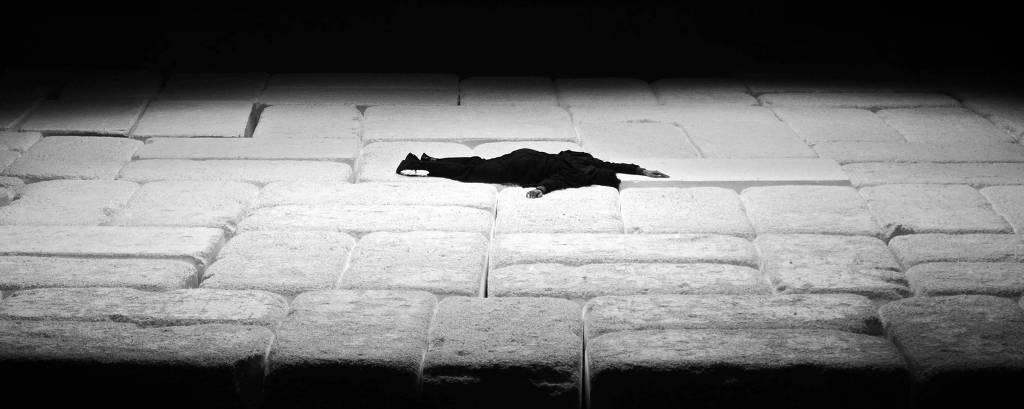 Foto de uma cena da peça 'A Tragédia Latino Americana', com um homem deitado de barriga para baixo no palco. O entorno é escuro e a luz está sobre ele.