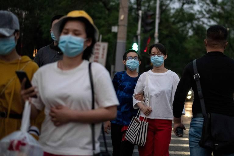 Pessoas com máscaras caminham em rua em Pequim