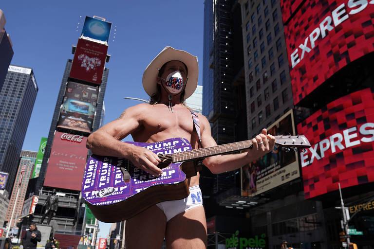 Robert Burck, conhecido como o Naked Cowboy, posa para fotos de máscara em Times Square, em Nova York