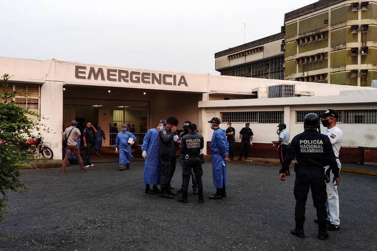 Policiais e profissionais da saúde esperam a chegada de presos em hospital de Guanare após rebelião na prisão de Los Llanos
