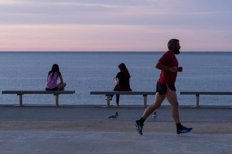 Duas mulheres mantêm o distanciamento social enquanto corredor passa por trás delas em Barcelona