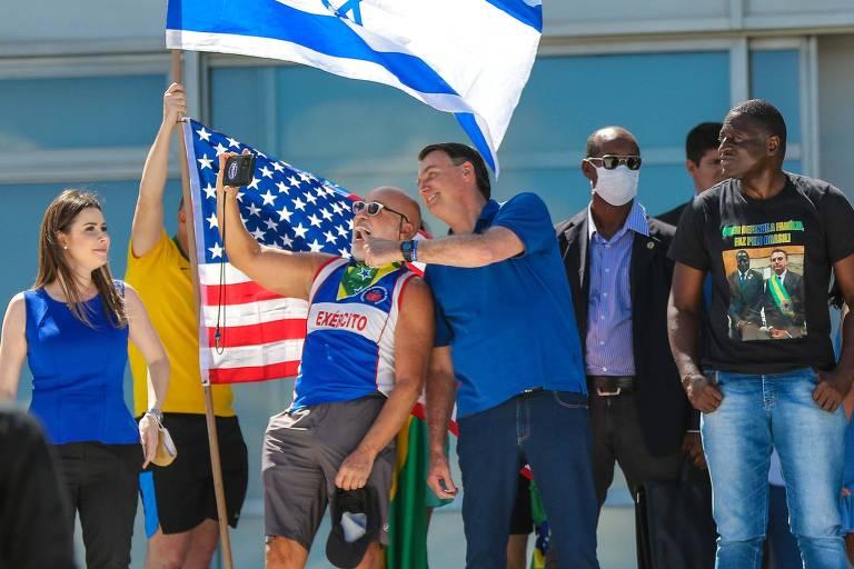 Bolsonaro, ao lado das bandeiras dos EUA e de Israel, com apoiadores no Planalto
