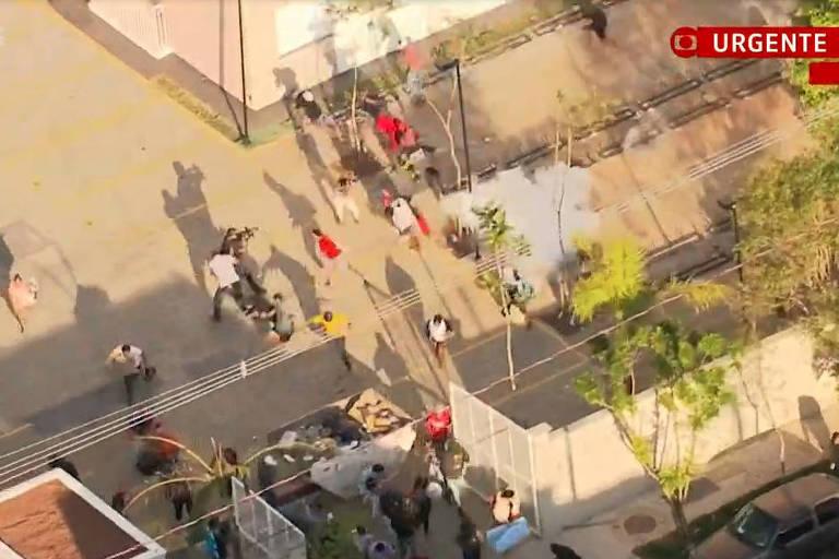 Imagens da GloboNews mostram os invasores correndo durante ação da polícia, que utilizou bombas de efeito moral