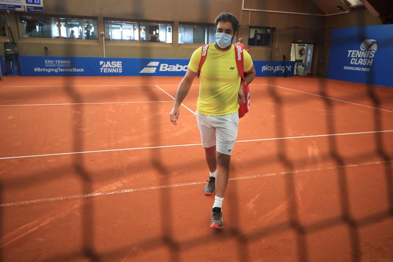 Tenista de máscara carrega seu equipamento de jogo atrás de uma rede