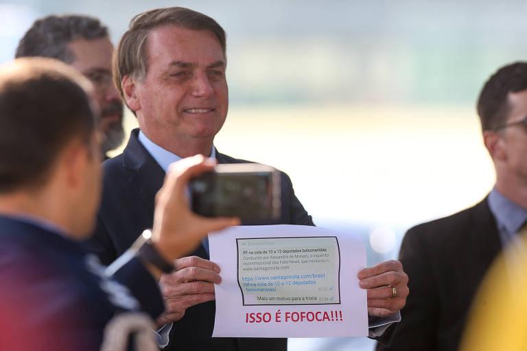O presidente Jair Bolsonaro mostra a apoiadores papel impresso com cópia de sua conversa com Moro que agora é alvo de investigação no STF (Supremo Tribunal Federal)