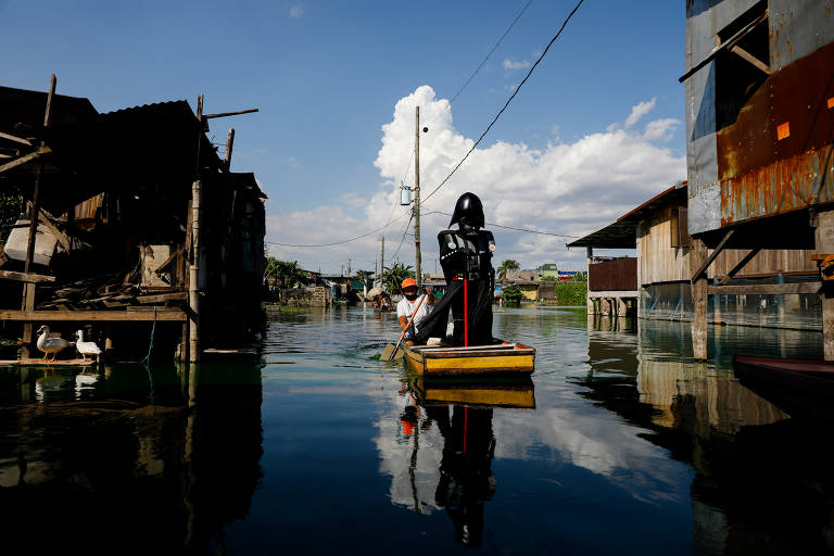Um oficial da vila vestido como Darth Vader, personagem de Star Wars, em um pequeno barco para entregar bens de socorro a residentes no complexo Artex inundado em Malabon, Metro Manila, Filipinas