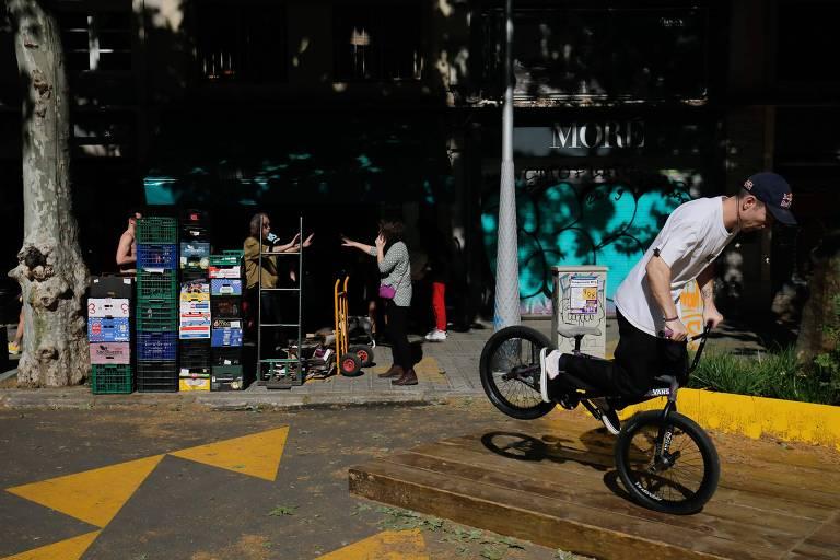 Jovem faz manobra com bicicleta em Barcelona, em meio à pandemia de coronavírus