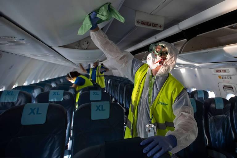 Homem com colete e máscara de proteção limpa compartimento de malas em cabine de avião