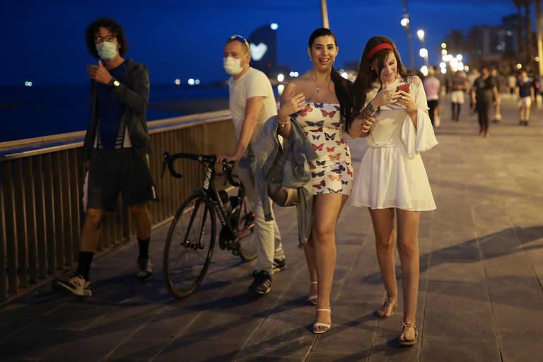 À noite, duas mulheres estão de braços dados andando em um calçadão beira mar. Ao lado delas. há um homem de roupas pretas usando máscara  e um senhor segurando sua bicicleta, também de máscara