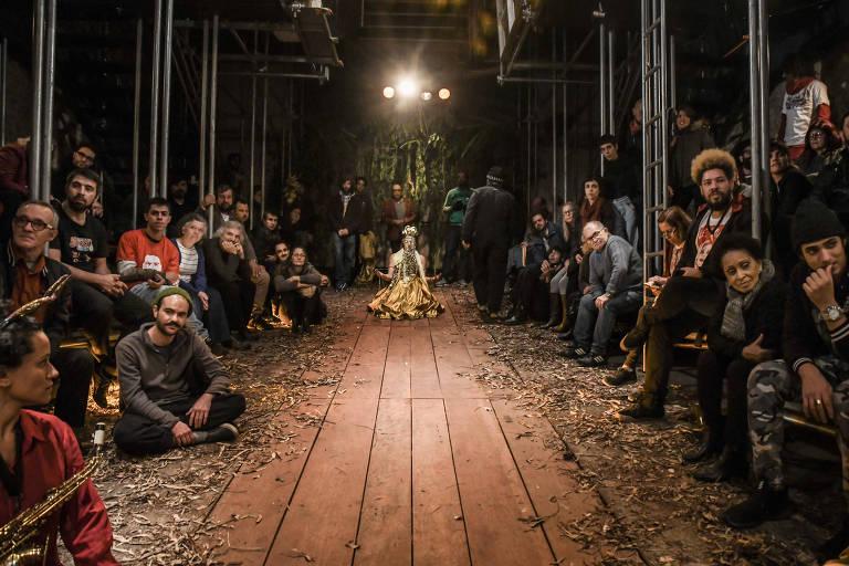 Corredor de madeira no meio, público sentado ao lado
